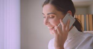 Portrait de plan rapproché de la jeune femme d'affaires ayant un appel téléphonique parlant gaiement le regard par la fenêtre dan banque de vidéos