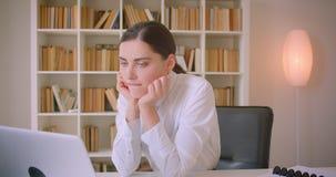 Portrait de plan rapproché de la jeune femme d'affaires caucasienne attirante ayant un faire appel visuel à l'ordinateur portable clips vidéos