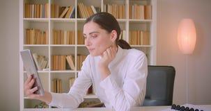 Portrait de plan rapproché de la jeune femme d'affaires caucasienne ayant un faire appel visuel au comprimé ondulant salut et par clips vidéos
