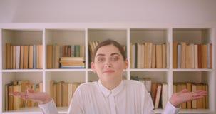 Portrait de plan rapproché de la jeune femme d'affaires caucasienne drôle regardant la caméra souriant gaiement se tenant dans le banque de vidéos