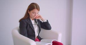 Portrait de plan rapproché de la jeune femme d'affaires caucasienne en verres lisant un livre se reposant dans le fauteuil dans l banque de vidéos