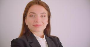 Portrait de plan rapproché de la jeune femme d'affaires caucasienne regardant la caméra souriant gaiement avec ses bras croisés a banque de vidéos
