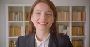 Portrait de plan rapproché de la jeune femme d'affaires caucasienne regardant la caméra souriant gaiement dans la bibliothèque à  banque de vidéos
