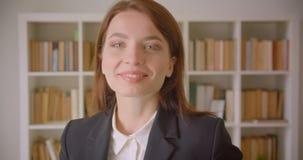Portrait de plan rapproché de la jeune femme d'affaires caucasienne regardant la caméra souriant gaiement dans la bibliothèque à  clips vidéos