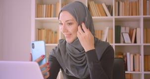 Portrait de plan rapproché de la jeune femme d'affaires musulmane attirante dans le hijab ayant un faire appel visuel au téléphon banque de vidéos
