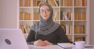 Portrait de plan rapproché de la jeune femme d'affaires musulmane attirante dans le hijab regardant la caméra souriant gaiement s clips vidéos