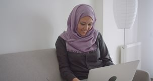 Portrait de plan rapproché de la jeune femme d'affaires musulmane dans le hijab dactylographiant sur l'ordinateur portable regard clips vidéos