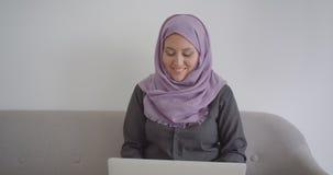 Portrait de plan rapproché de la jeune femme d'affaires musulmane dans le hijab utilisant l'ordinateur portable regardant la camé clips vidéos