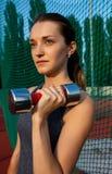 Portrait de plan rapproché de la jeune fille sportive faisant des exercices avec le d Photo stock