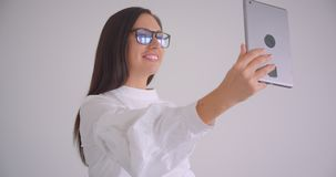 Portrait de plan rapproché de la jeune jolie femme d'affaires caucasienne en verres ayant un faire appel visuel au comprimé parla clips vidéos