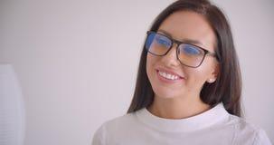 Portrait de plan rapproché de la jeune jolie femme d'affaires caucasienne en verres regardant la caméra souriant gaiement avec le clips vidéos