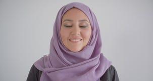 Portrait de plan rapproché de la jeune jolie femme musulmane dans le hijab regardant la caméra souriant gaiement avec le fond d'i banque de vidéos
