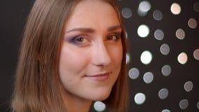 Portrait de plan rapproch? de la jeune jolie fille caucasienne regardant la cam?ra et souriant joyeux avec le fond de bokeh banque de vidéos