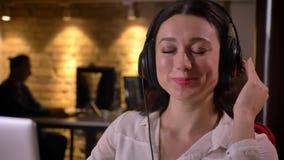 Portrait de plan rapproché de la jeune musique de écoute femelle heureuse d'employé de bureau dans les écouteurs souriant et rega clips vidéos