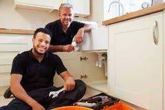 Portrait de plombier avec l'apprenti dans la cuisine domestique Images stock