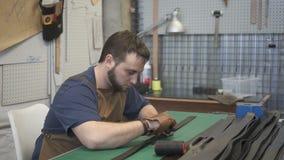 Portrait de poignée de couture de sac de spécialiste en cuir masculin dans l'atelier banque de vidéos