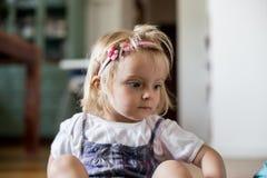 Portrait de port triste ou pensant sérieux de bandeau de jeune fille blonde caucasienne de bébé à la maison Photo stock