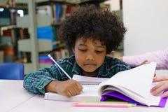 Portrait de professeur aidant le petit garçon avec le travail dans le Li Photos stock
