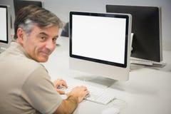 Portrait de professeur heureux travaillant sur l'ordinateur Photographie stock libre de droits