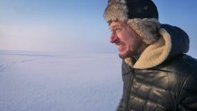 Portrait de profil du fonctionnement fastly et homme criard dans le chapeau de fourrure et le manteau chaud sur le champ de neige banque de vidéos