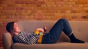 Portrait de profil de plan rapproché du jeune joli défilement de fille sur le comprimé et de rire gaiement le mensonge sur le sof banque de vidéos