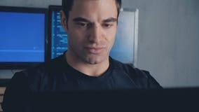 Portrait de programmeur de promoteur travaillant sur l'ordinateur à un centre de traitement des données rempli d'écrans de monite clips vidéos