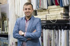 Portrait de propriétaire heureux d'homme d'affaires avec les bras croisés dans le magasin intérieur de tissus, échantillons de ti images stock