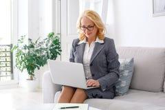 Portrait de psychologue de femme se reposant au siège social occasionnel travaillant à l'ordinateur portable photographie stock libre de droits