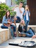Portrait de quatre adolescents jouant la musique ensemble dehors Image stock