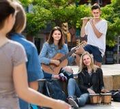 Portrait de quatre adolescents jouant la musique ensemble dehors Photographie stock libre de droits