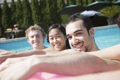 Portrait de quatre amis dans la piscine avec un radeau gonflable Photo libre de droits