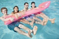 Portrait de quatre amis dans la piscine avec un radeau gonflable Images stock