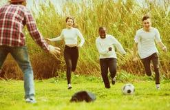 Portrait de quatre amis posant sur le champ de campagne avec la boule Photos stock