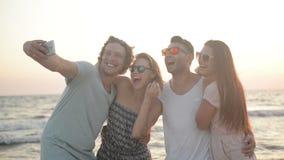 Portrait de quatre amis prenant Selfie utilisant Smartphone ensemble sur le bord de la mer pendant la Windy Weather banque de vidéos