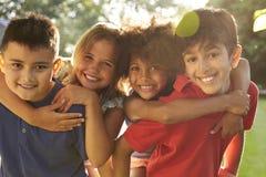 Portrait de quatre enfants ayant l'amusement dehors ensemble Photos stock