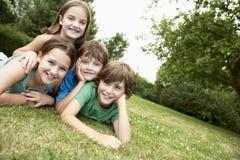 Portrait de quatre enfants se situant en parc Images stock
