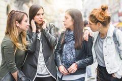 Portrait de quatre jolis amie, bavardage sur la rue Photographie stock