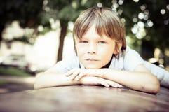Portrait de rêver le petit garçon 7 années dehors Photographie stock