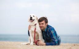 Portrait de ressort d'un jeune homme avec un chien sur la plage Photos stock