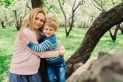 Portrait de ressort de la mère enceinte heureuse appréciant le jour chaud avec le fils d'enfant Photographie stock
