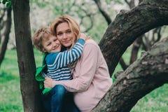 Portrait de ressort de la mère enceinte heureuse appréciant le jour chaud avec le fils d'enfant Photos stock