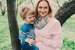Portrait de ressort de la mère enceinte heureuse appréciant le jour chaud avec le fils d'enfant Images libres de droits