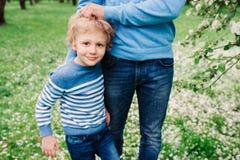 Portrait de ressort du garçon heureux d'enfant appréciant la promenade avec le père dans le jardin de floraison de pomme Photographie stock