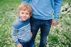Portrait de ressort du garçon heureux d'enfant appréciant la promenade avec le père dans le jardin de floraison de pomme Photos libres de droits