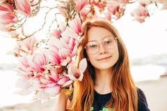 Portrait de ressort de fille de la préadolescence rousse adorable d'enfant avec des fleurs de magnolia photographie stock