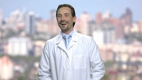 Portrait de rire l'homme mûr dans le manteau blanc banque de vidéos