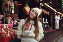 Portrait de rue de la belle jeune femme de sourire tenant des cannes de sucrerie et regardant l'appareil-photo Madame portant sti image stock