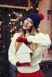 Portrait de rue de la belle jeune femme de sourire tenant la maison en bois de jouet Madame portant l'hiver classique élégant tri Photographie stock libre de droits