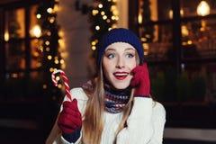 Portrait de rue de nuit de la belle jeune femme de sourire parlant du téléphone portable et regardant de côté Classique de port d Image libre de droits