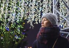 Portrait de rue de jeune belle femme Lumières de fête de guirlande Effet de chutes de neige photographie stock libre de droits